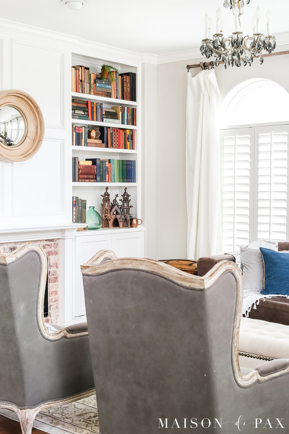 gray wingback chairs in front of a white fireplace and bookcase