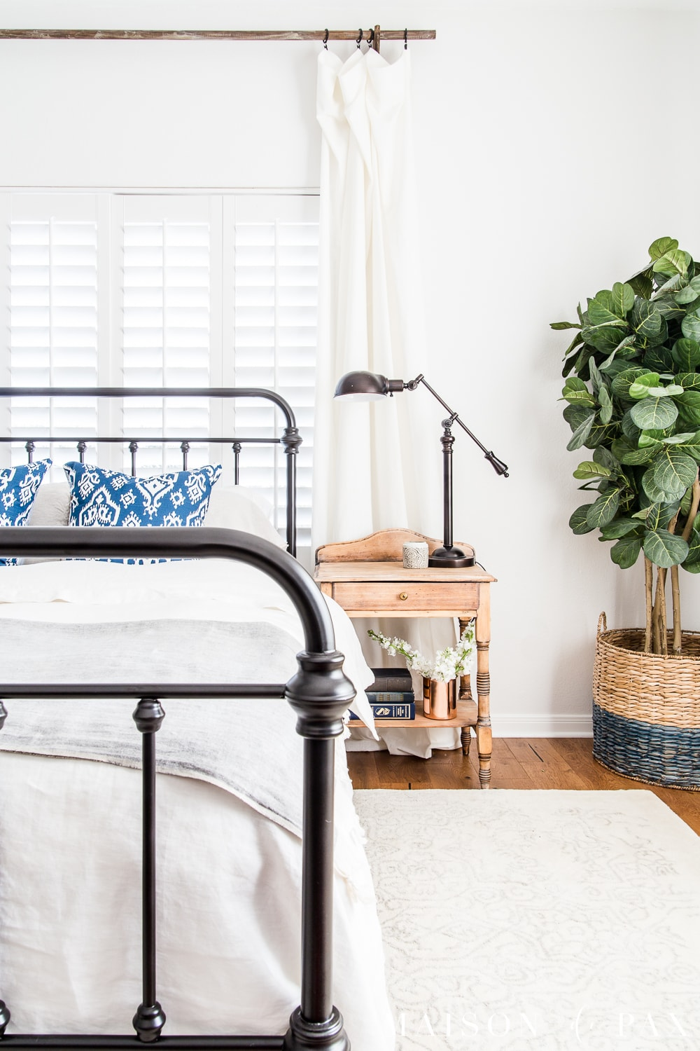 Love the iron bed and raw wood nightstand! Looking to add a seasonal touch to your bedroom?  Don't miss these incredibly simple master bedroom decorating ideas for spring! #springdecor #springbedroom #nightstand #modernfarmhouse
