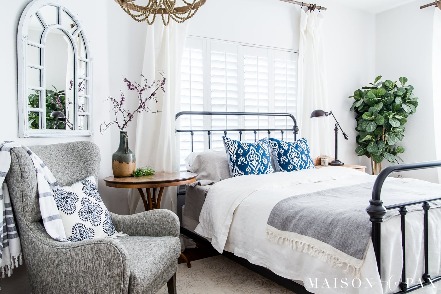 Mostly white bedroom with pops of blue for spring/summer... Looking to add a seasonal touch to your bedroom?  Don't miss these incredibly simple master bedroom decorating ideas for spring! #springdecor #springbedroom #nightstand #modernfarmhouse