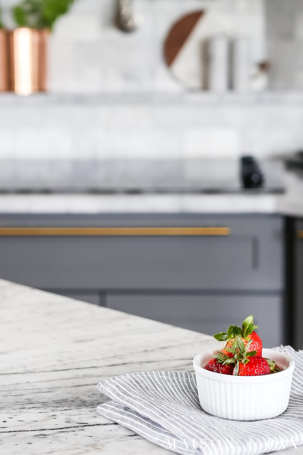 Close-up of a bowl of strawberries on a gray and white marble countertop- Maison de Pax
