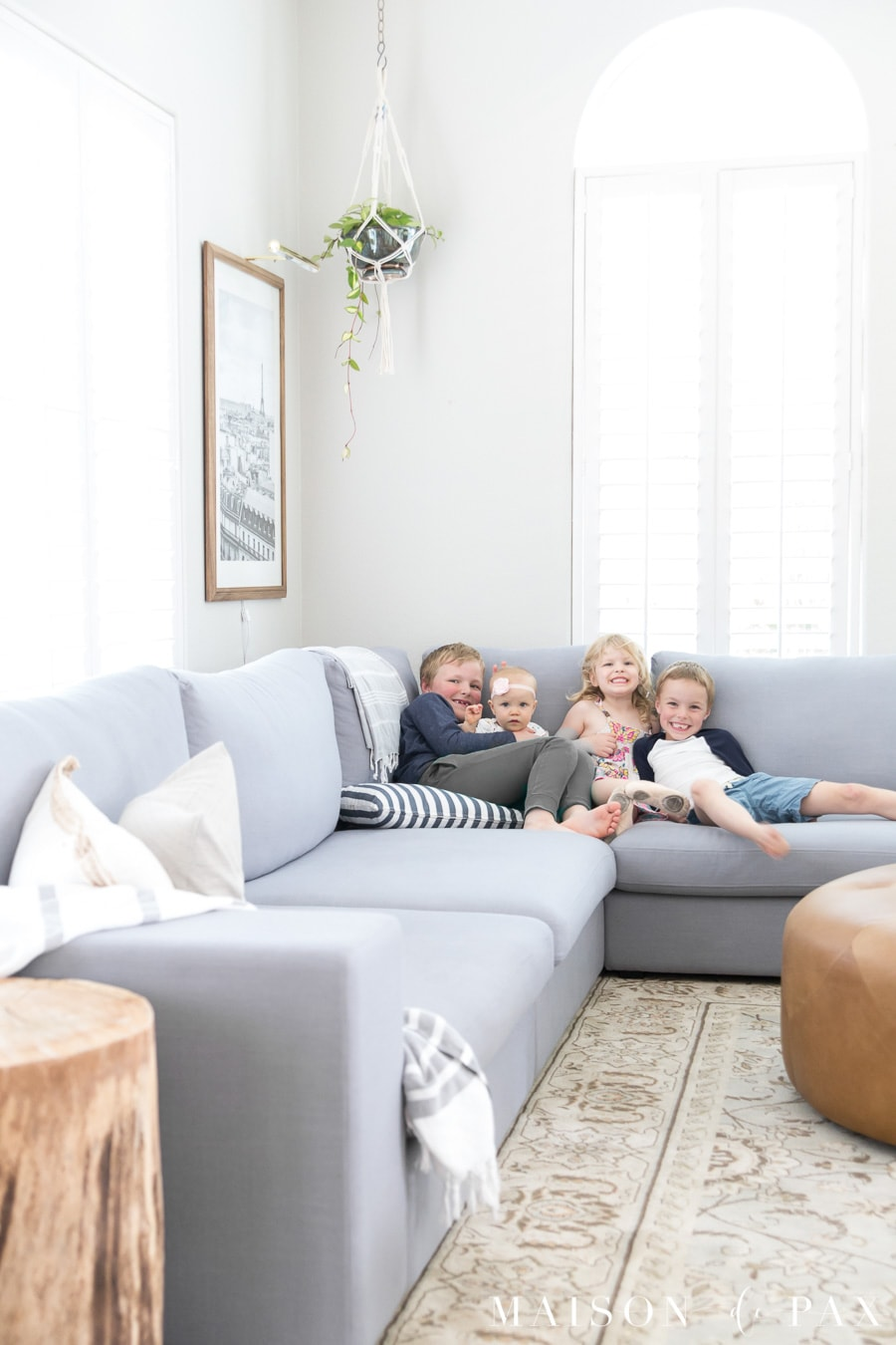 This huge gray sectional is perfect for a family room! Find out how to decorate a living room and create a light, bright feeling even with a large sectional. #livingroom #sectionalsofa #familyroom #familyroomdecor #livingroomdecor #decoratingsectionalsofa #modularsofa #lightgraysectional #graysectional #lightbrightdecor #decoratingwithkids #familyfriendlydecor