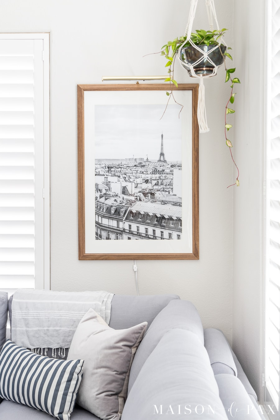 Find out the secret to inexpensive large wall art! This black and white photo is beautiful in a natural wood frame with a brass picture light above. #simplewallart #wallart #livingroomdecor