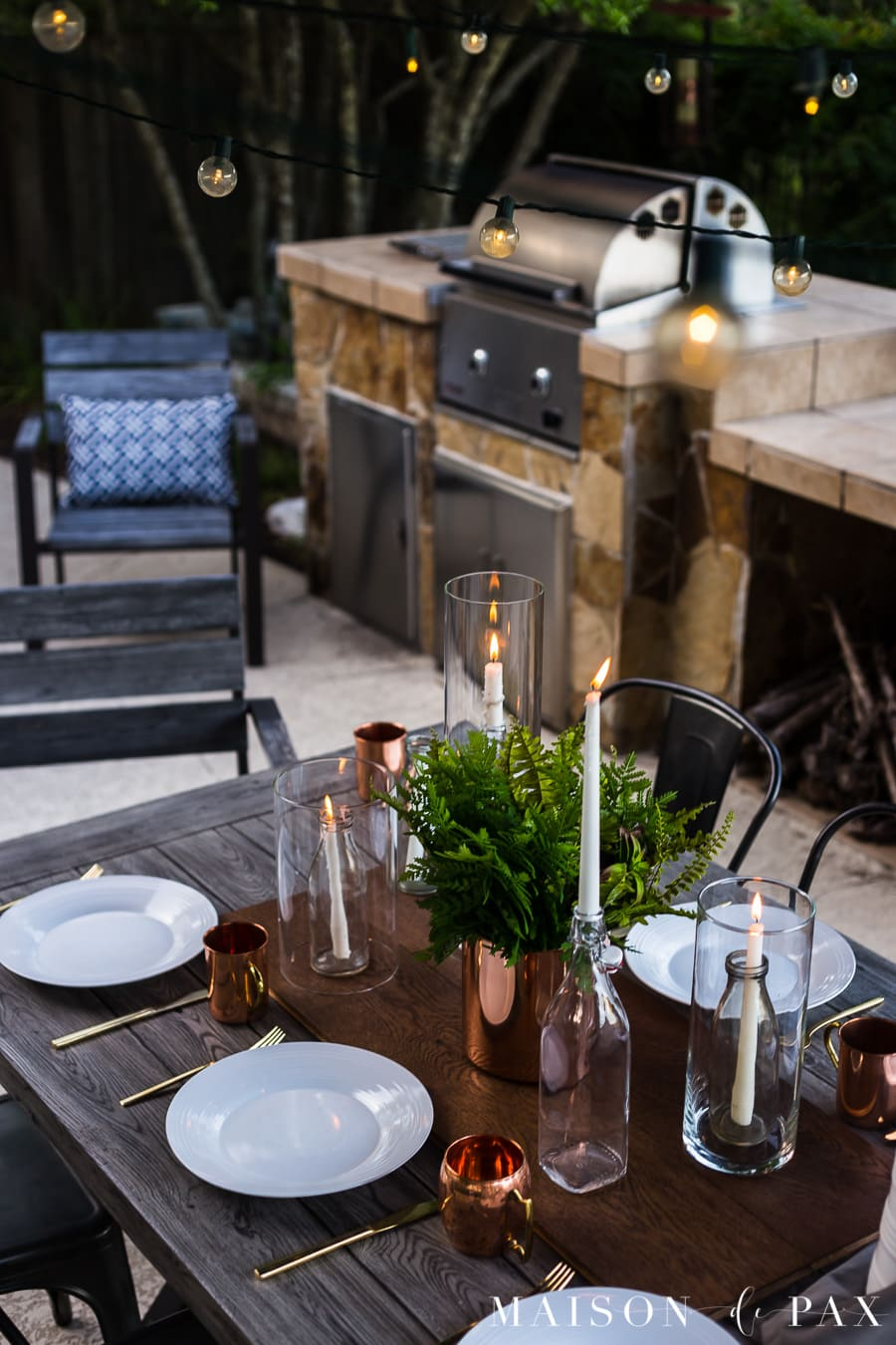String lights and candles make this outdoor dining magical. Get more tips for outdoor summer dining! #outdoordining #outdoorentertaining #summerentertaining #stringlights