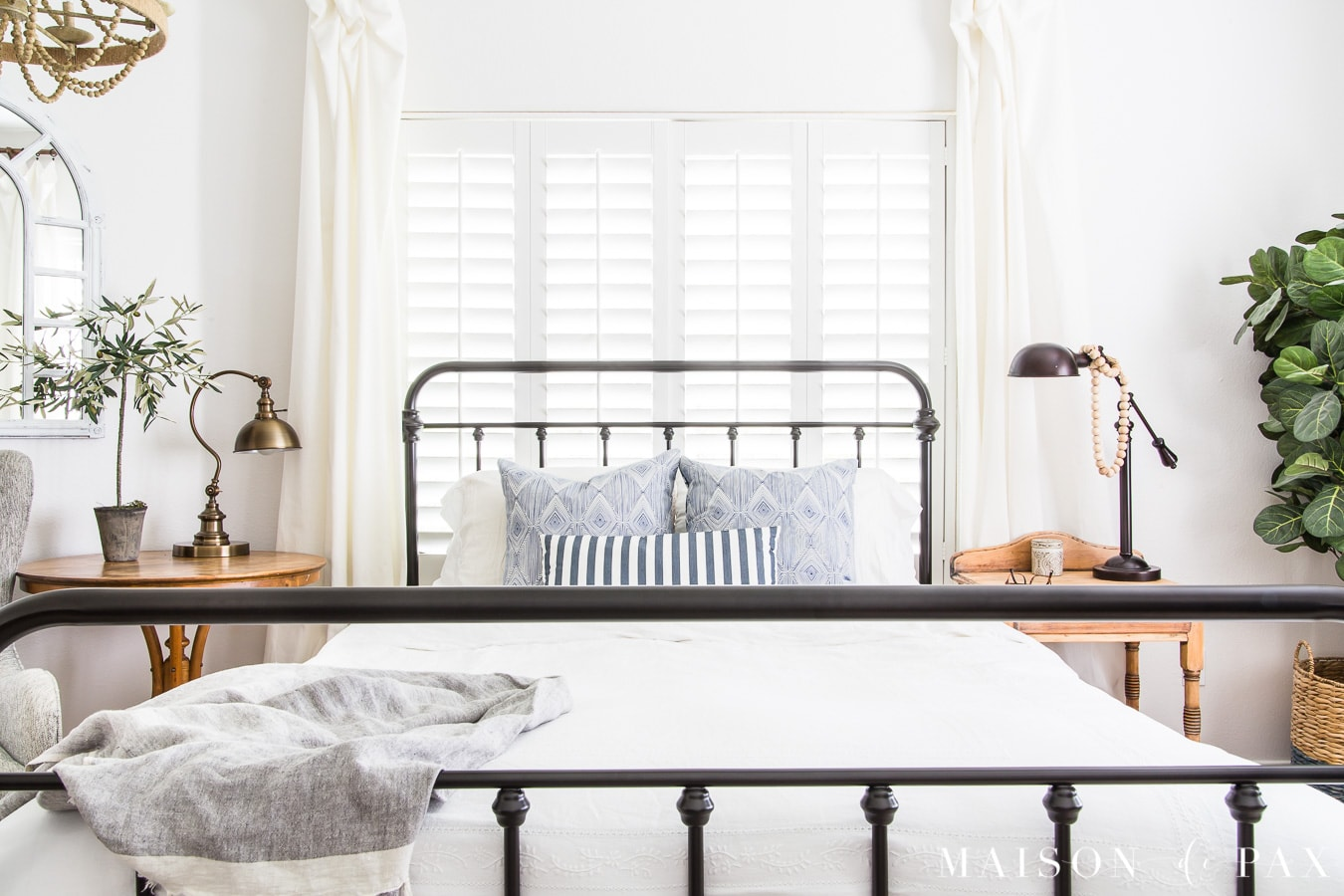 iron bed with white bedding and blue striped pillows