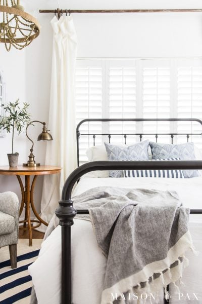 Click for blue and white master bedroom ideas! Simple, casual farmhouse charm. #bedroom #masterbedroom #ironbed #bedroomdecor #bedroomdecoratingideas #bedroomideas #summerdecor #bluewhitestripes