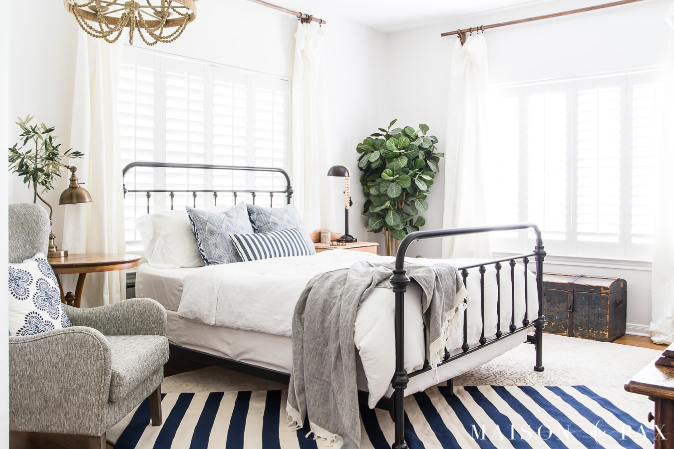 Navy And White Striped Rug Layered In Bedroom