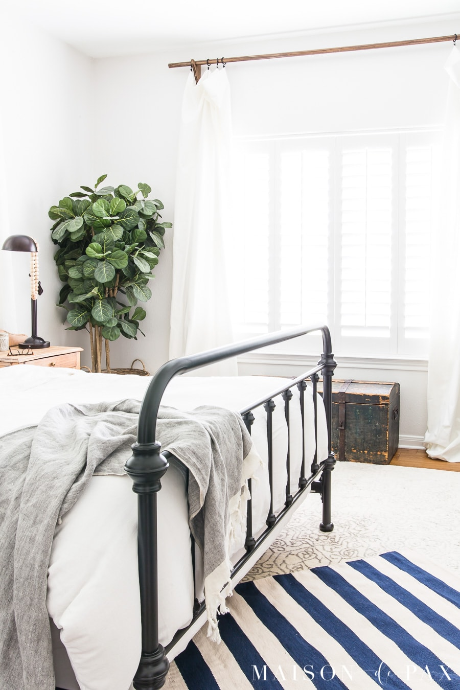 Get blue and white bedroom decorating ideas! #layeredrugs #bluewhite #bedroomdecor #bedroomdecoratingideas #whitebedding #ironbed #farmhousestyle