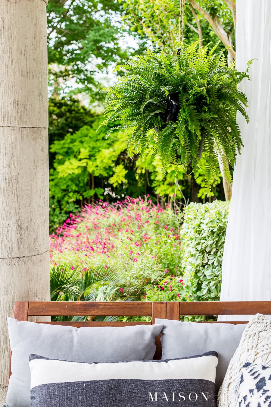 beautiful large fern hanging above an outdoor sofa on a covered patio | Maison de Pax