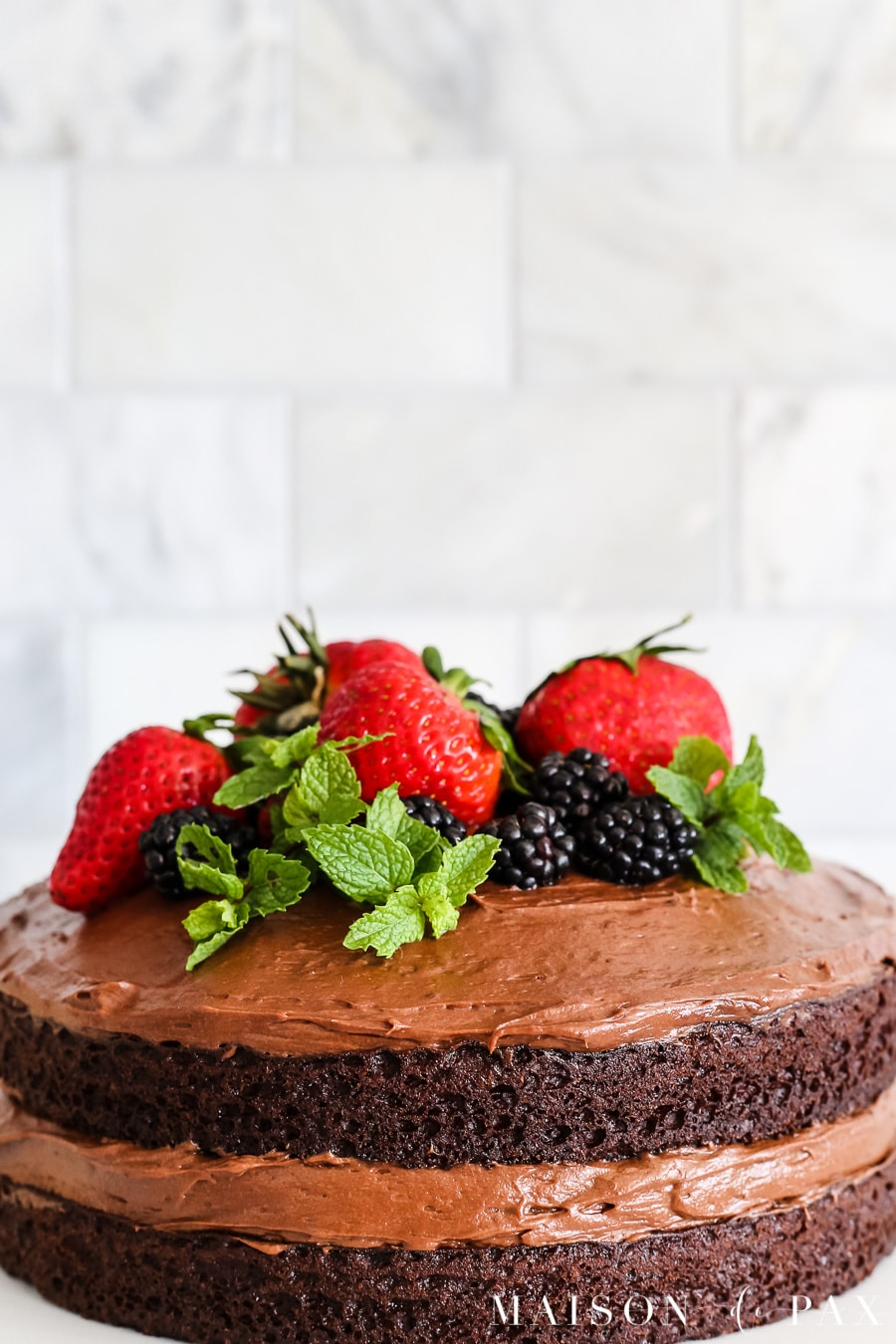 Chocolate naked cake with fruit on top! Learn how to make a naked cake. #nakedcake #nakedcakerecipe #cakefrosting #howtofrost #cakerecipe #creamcheesefrosting #cakedecorating #chocolatecake