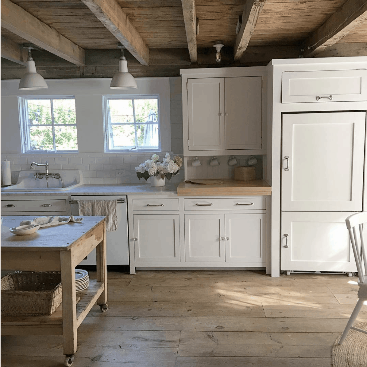 White Flower Farmhouse kitchen: rustic wood floors, white cabinets, marble counters, exposed ceiling beams- Maison de Pax