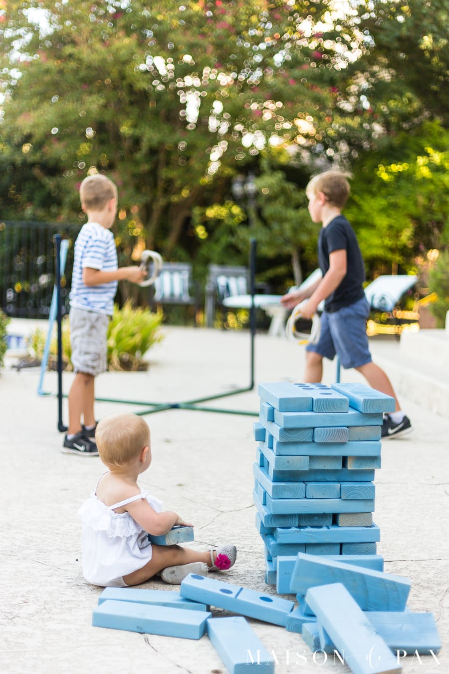baby sitting by giant Jenga game with boys playing ring toss in background | Maison de Pax