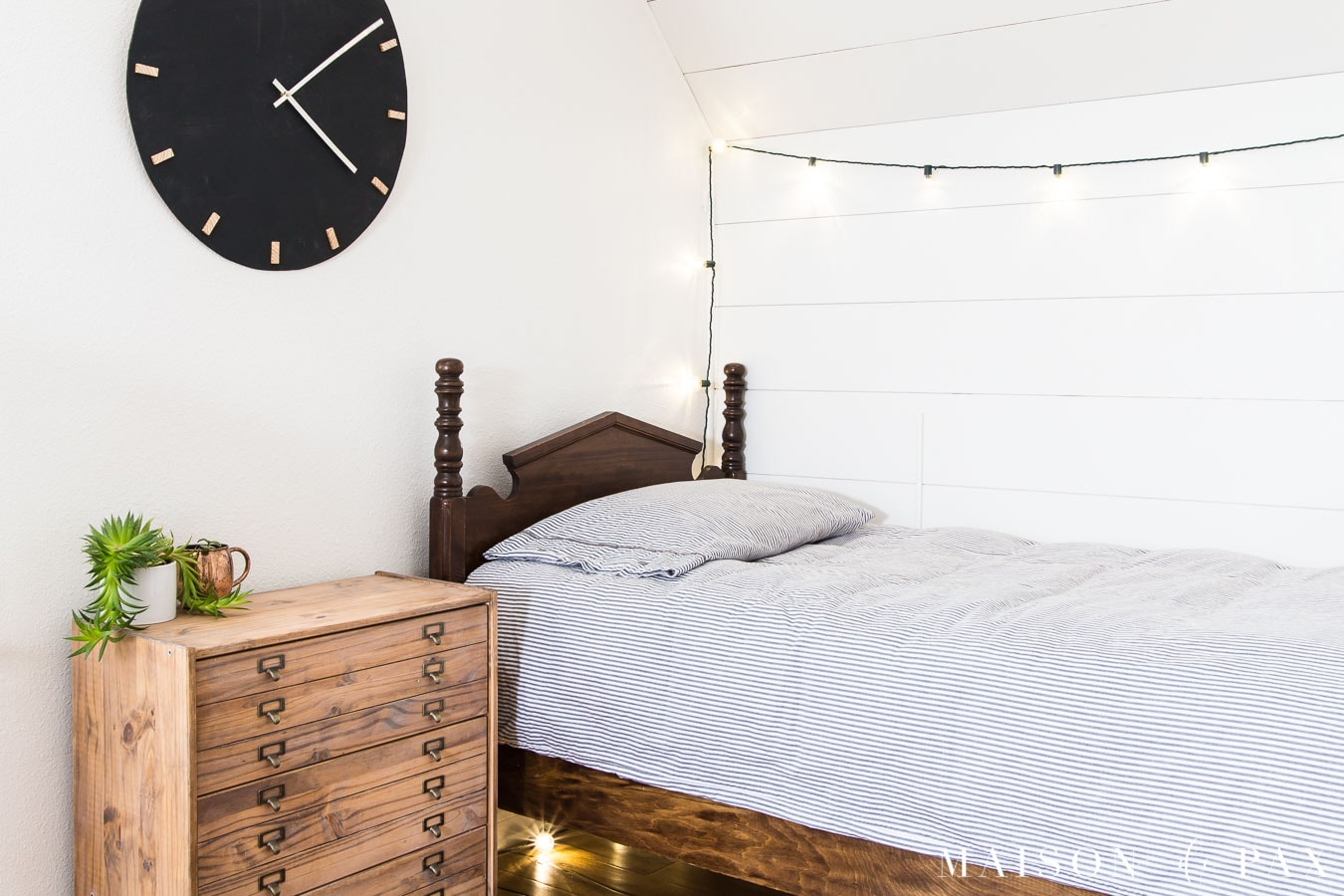 white bedroom with planked wall, antique twin bed, and printer's cabinet nightstand
