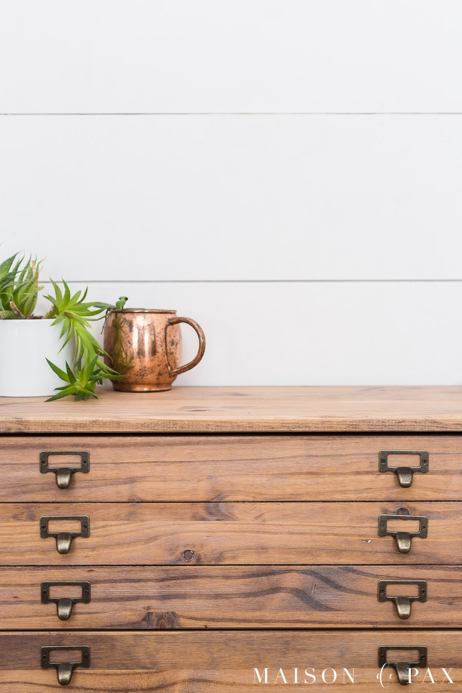 medium rustic wood, tiny drawers, and library pulls give a dresser an antique printer's cabinet look