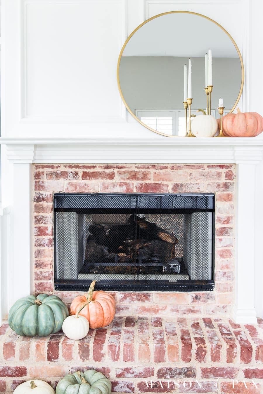 white mantel with red brick fireplace decorated with green and pink heirloom pumpkins