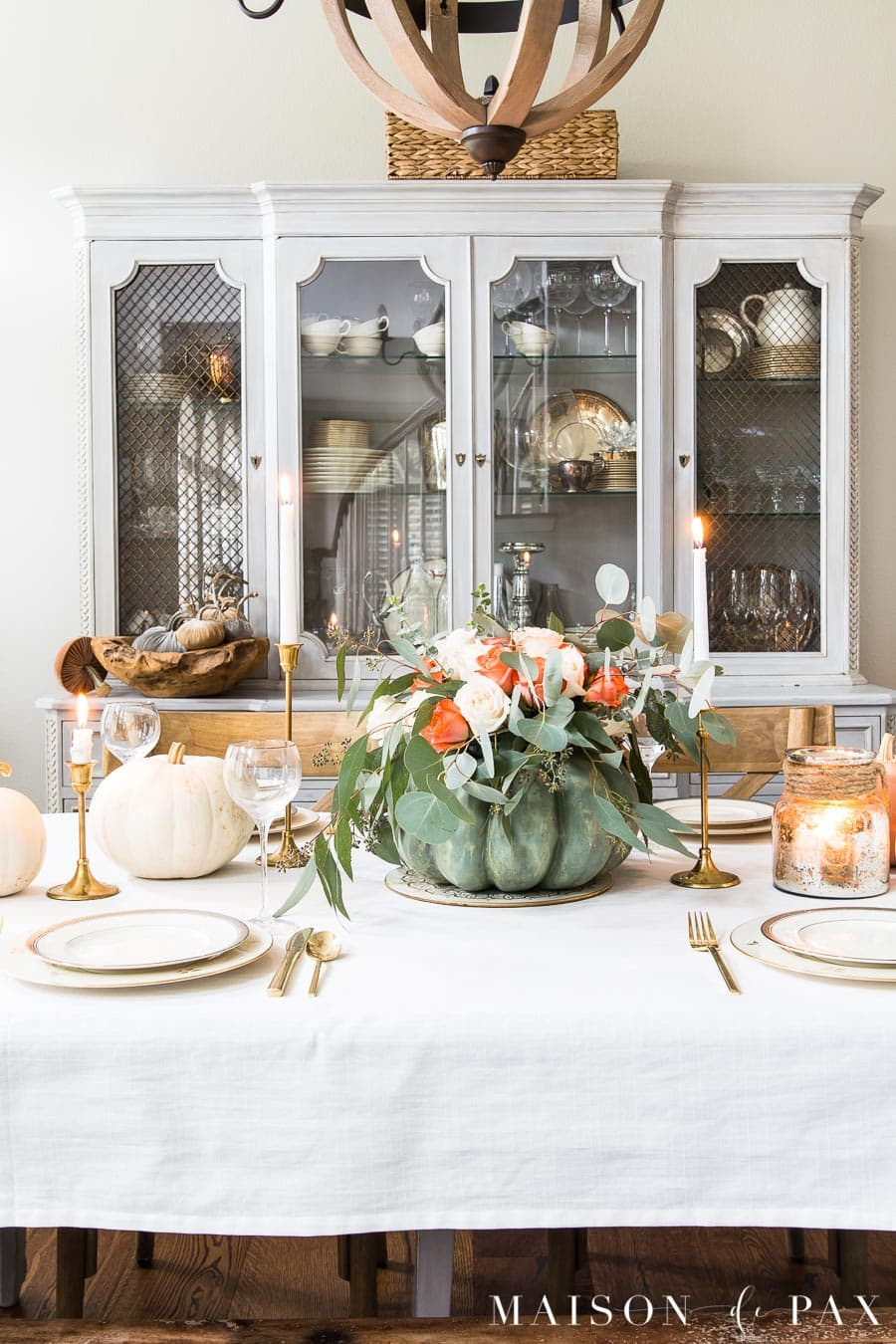 french country china hutch behind an elegant Thanksgiving table with white tablecloth, pumpkin centerpiece, and gold and silver china