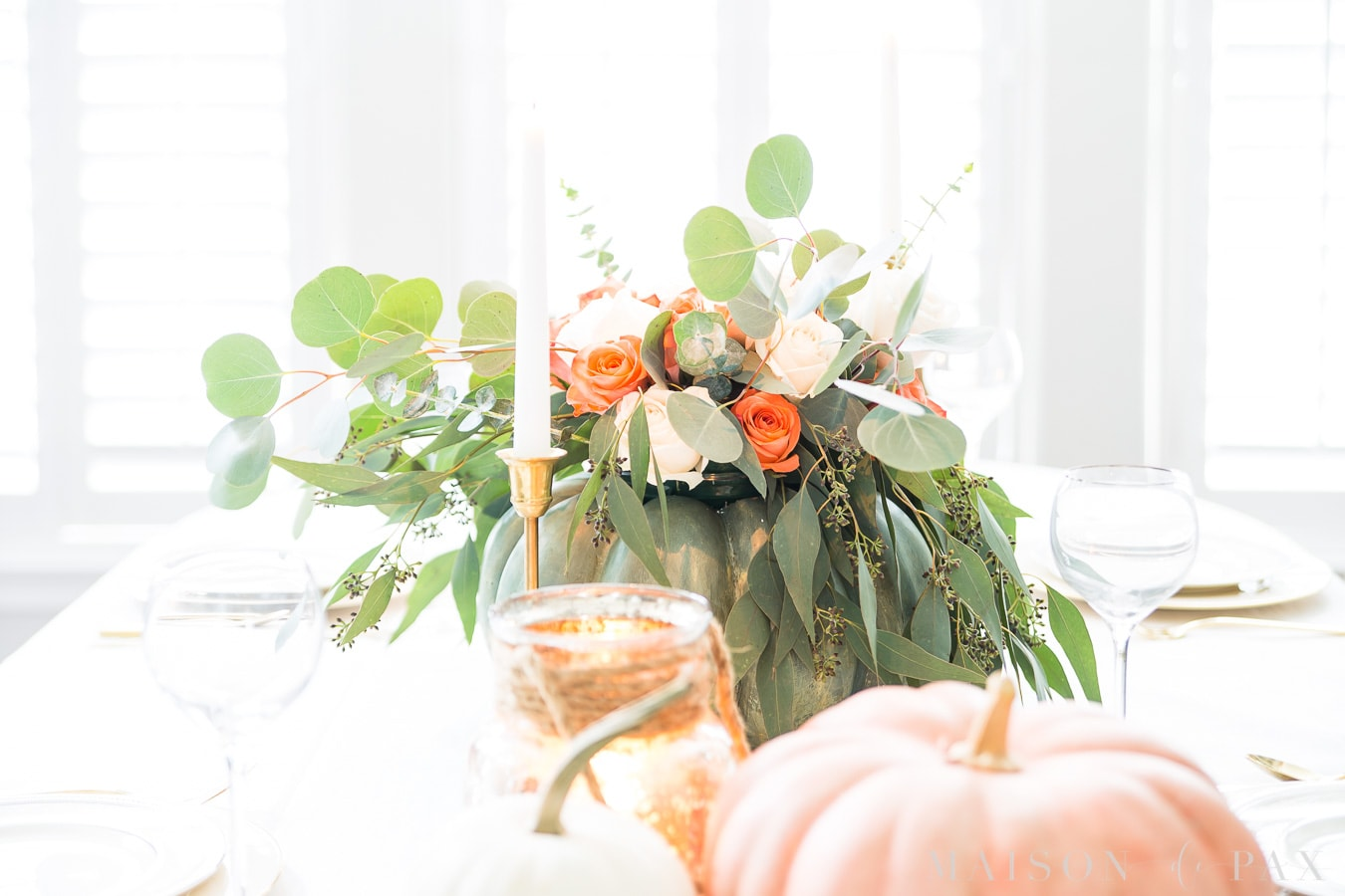 pumpkin floral centerpiece with brass candlesticks and pink and white and green pumpkins