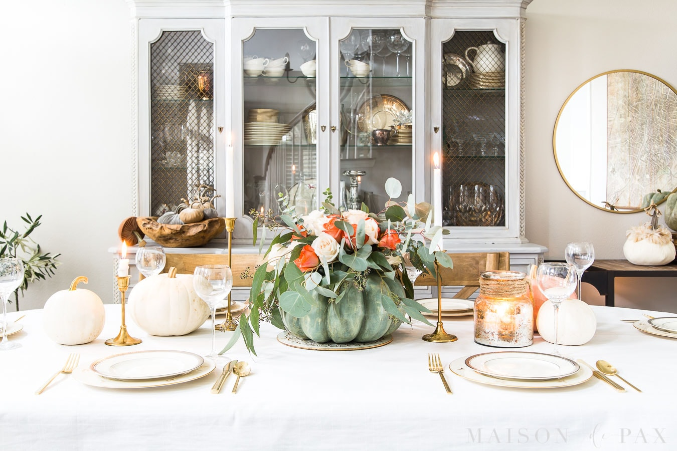 wide image of a Thanksgiving table with pumpkin floral centerpiece
