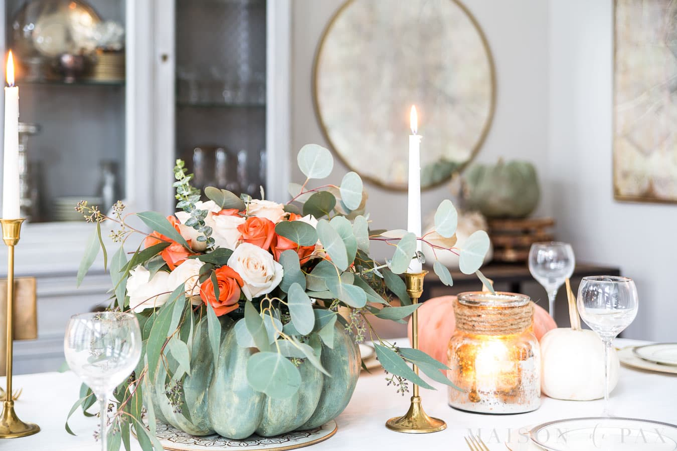 pumpkin with roses and eucalyptus, candles, and china creates an elegant Thanksgiving table.