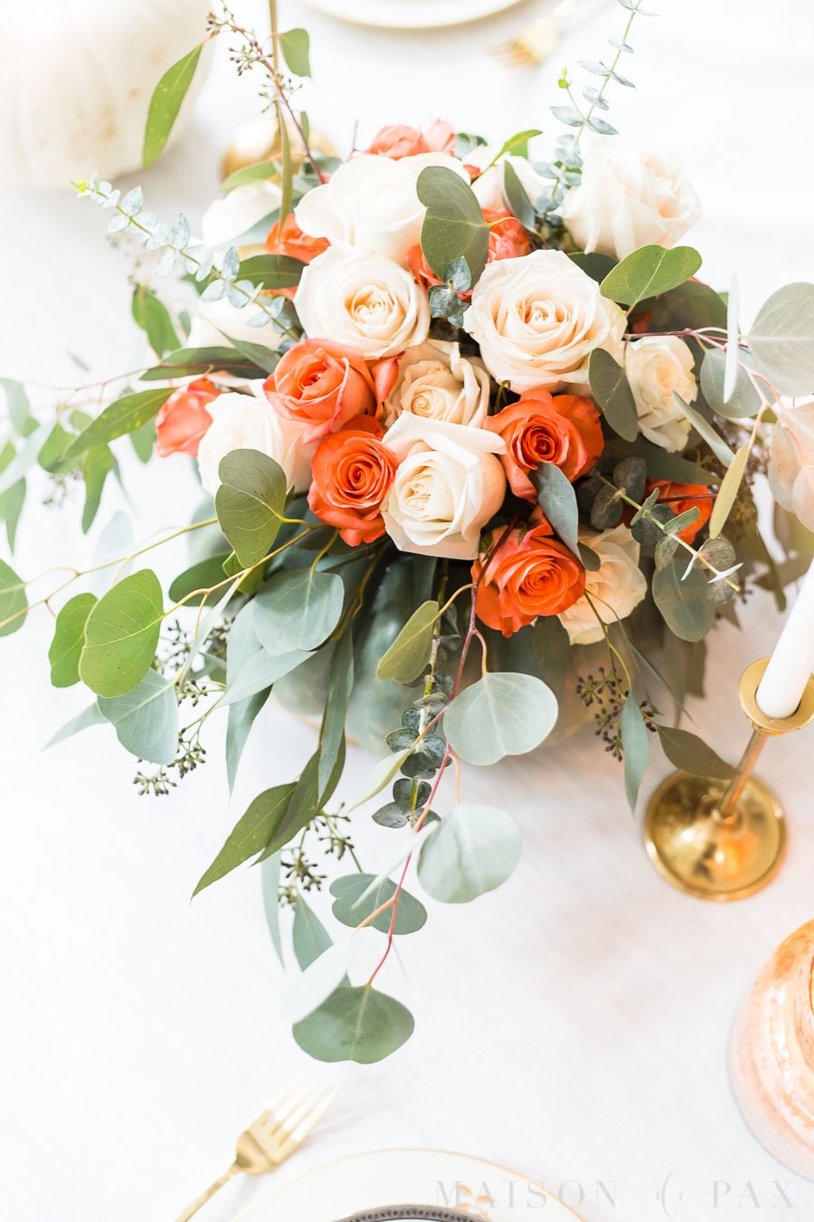 white and coral roses with seeded eucalyptus centerpiece