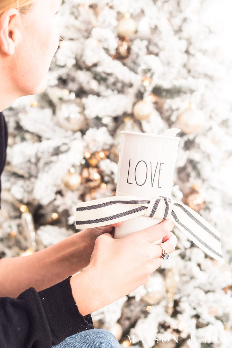 "woman sitting in front of Christmas tree holding a mug that reads ""love"""