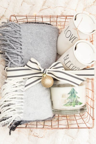 fringed wood throw blanket, travel mugs, and holiday candle in a copper wire gift basket tied with a bow