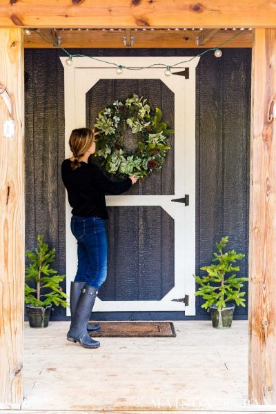 woman hanging wreath on black farmhouse exterior with white trim and holiday decor