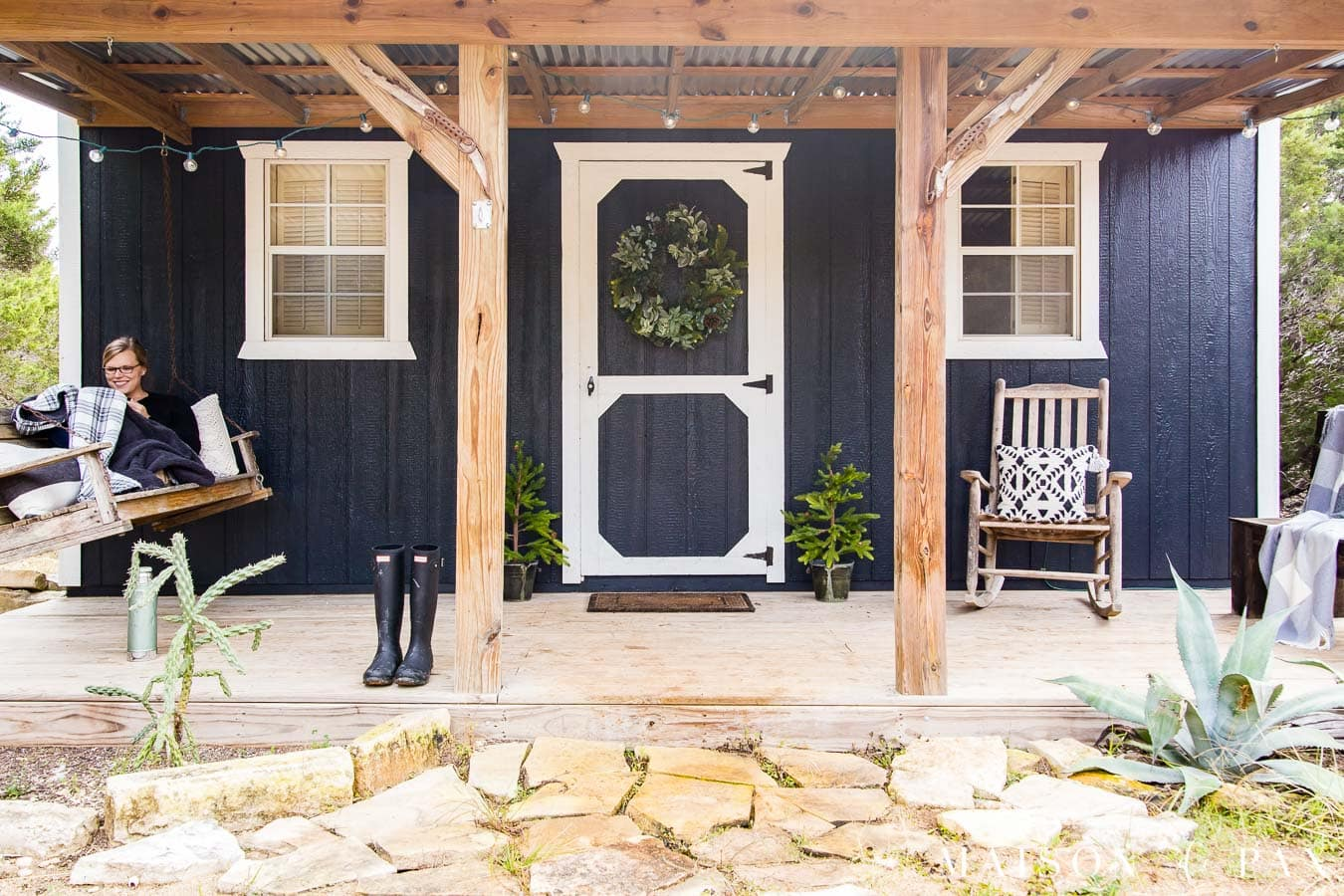 rustic front porch with cedar posts on a black tiny house with white trim