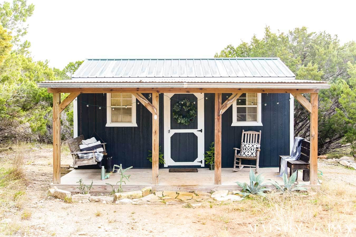 Black and white tiny house with deep front porch in the country