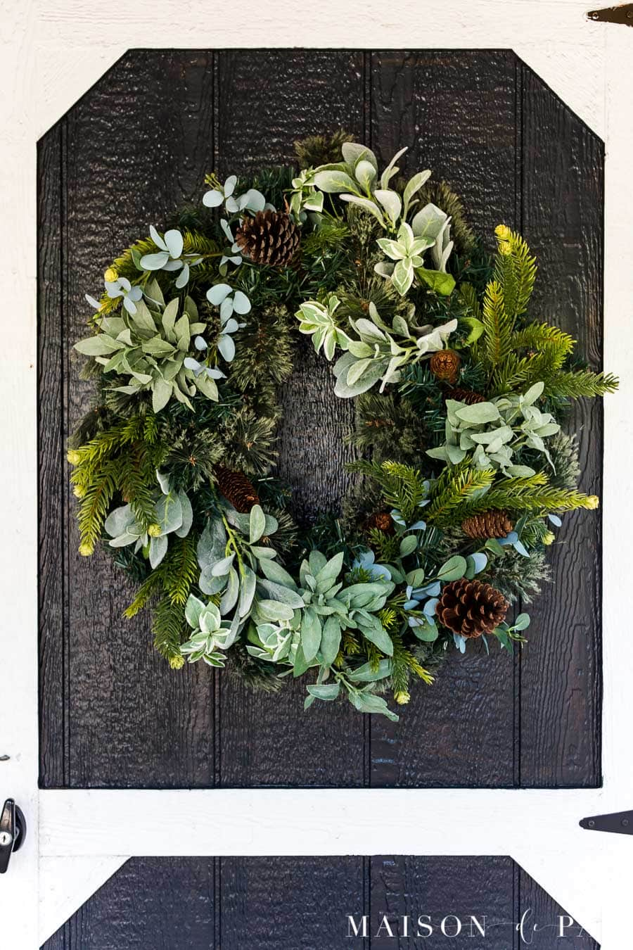 Full green wreath on a black barn door with white trim