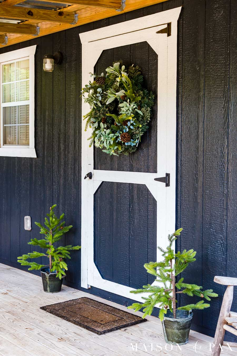 two tiny Christmas trees in rustic buckets on either side of the front door