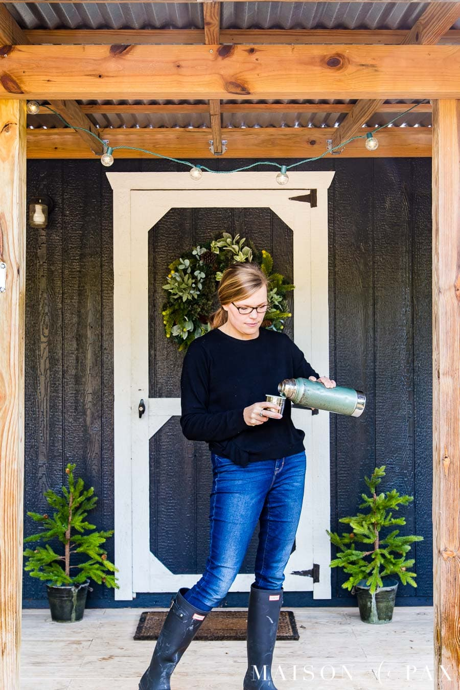 woman pouring coffee from an old thermos on the front porch of a black and white farmhouse