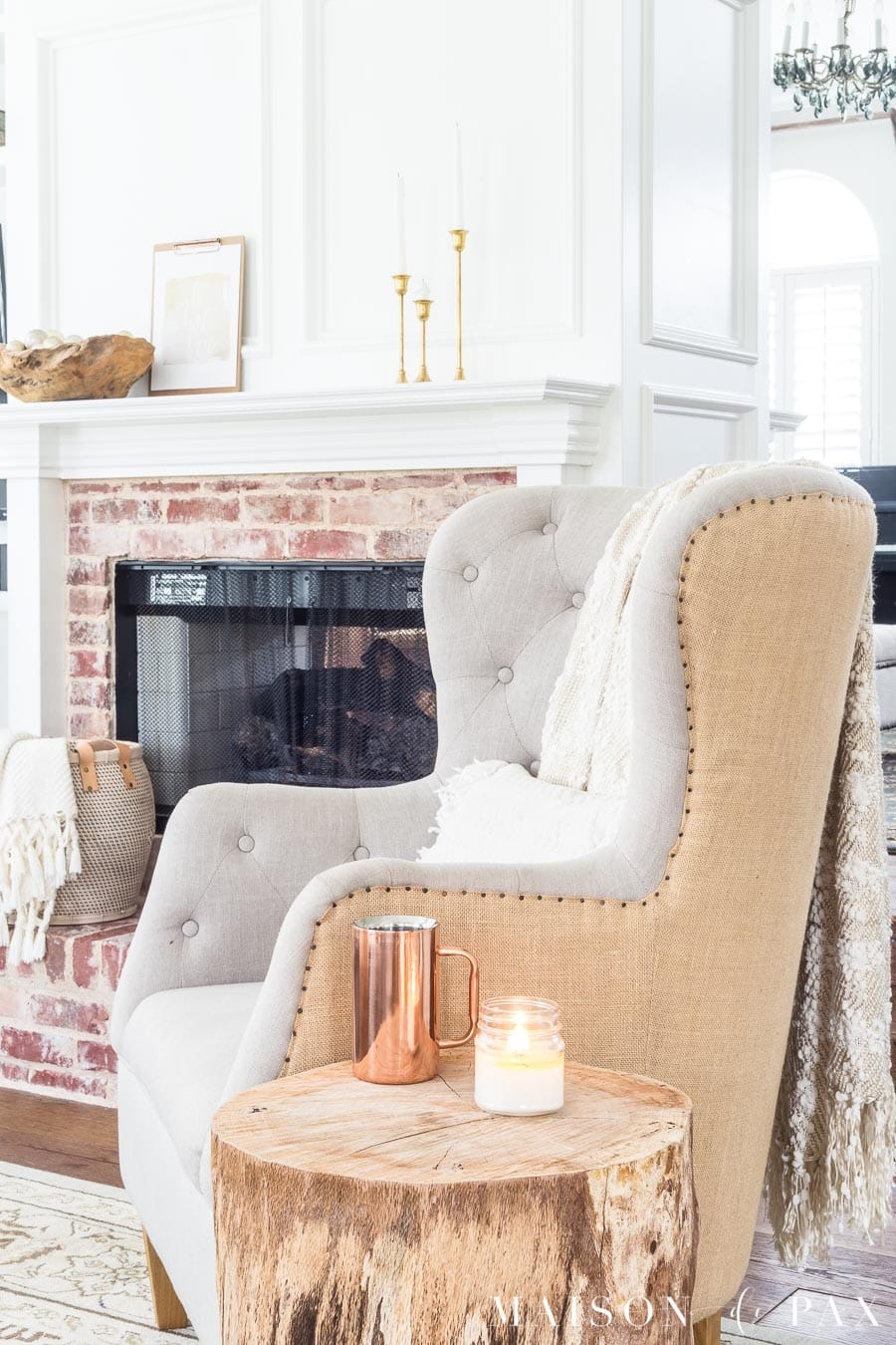 tufted armchair with log side table before a firplace with antique brick and white molding, all accented with gold and copper