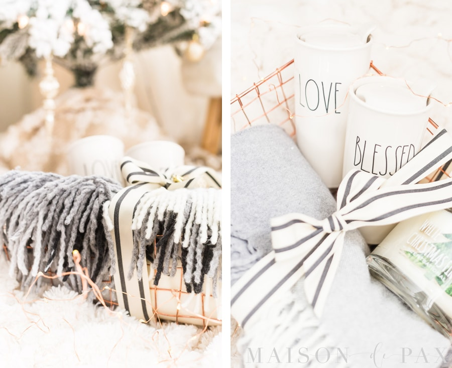 "travel mugs that read ""Love"" and ""Blessed"", a fringed wool throw, and a holiday candle in a copper wire basket"