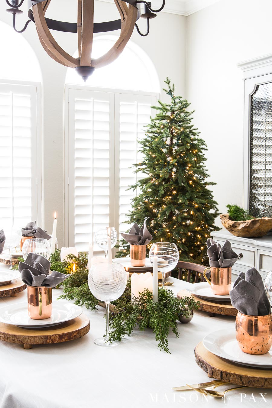 elegant green and copper holiday dining table with a simple green tree in the background