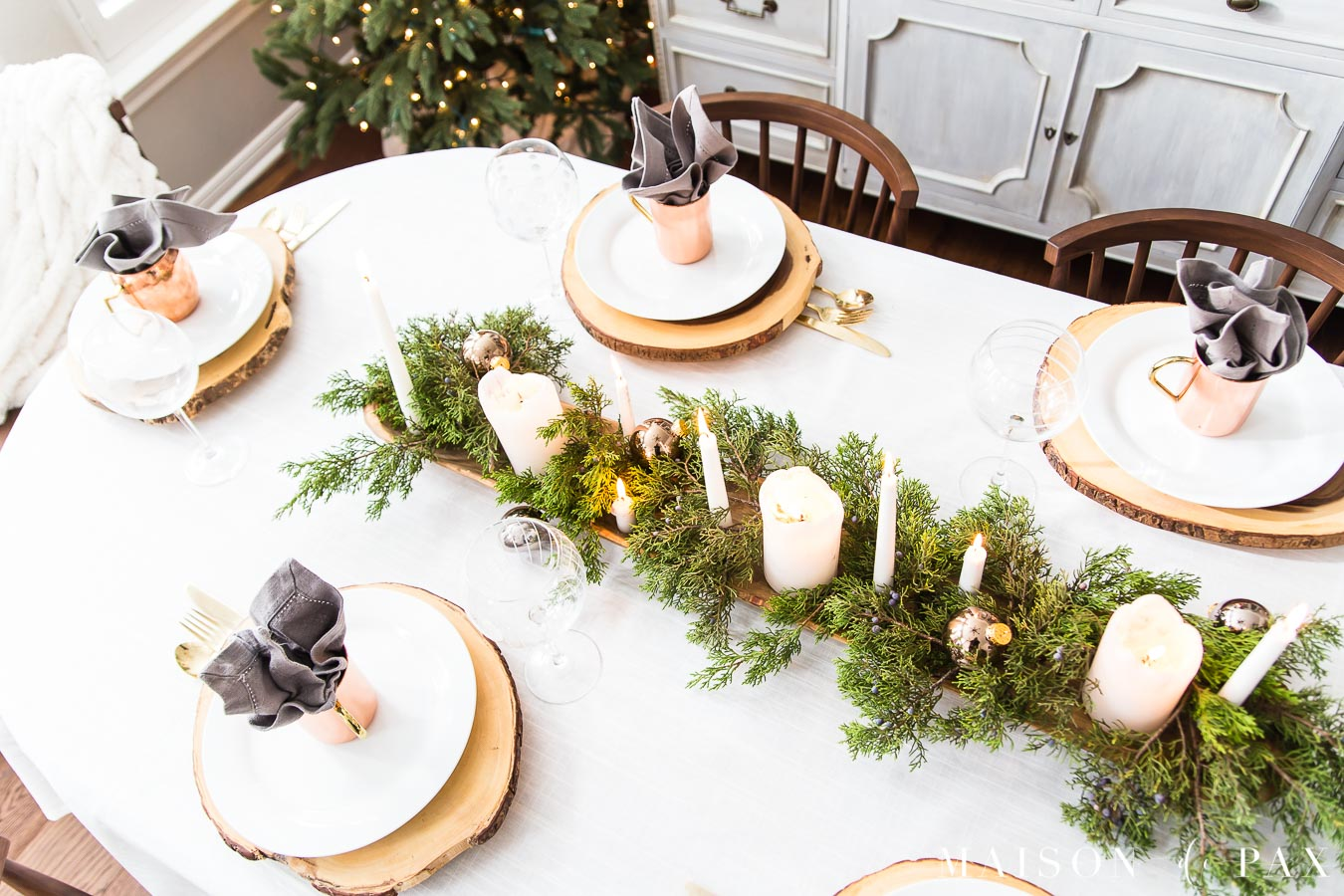 rustic wood log slice chargers under simple white plates create a rustic modern tablescape for the holidays