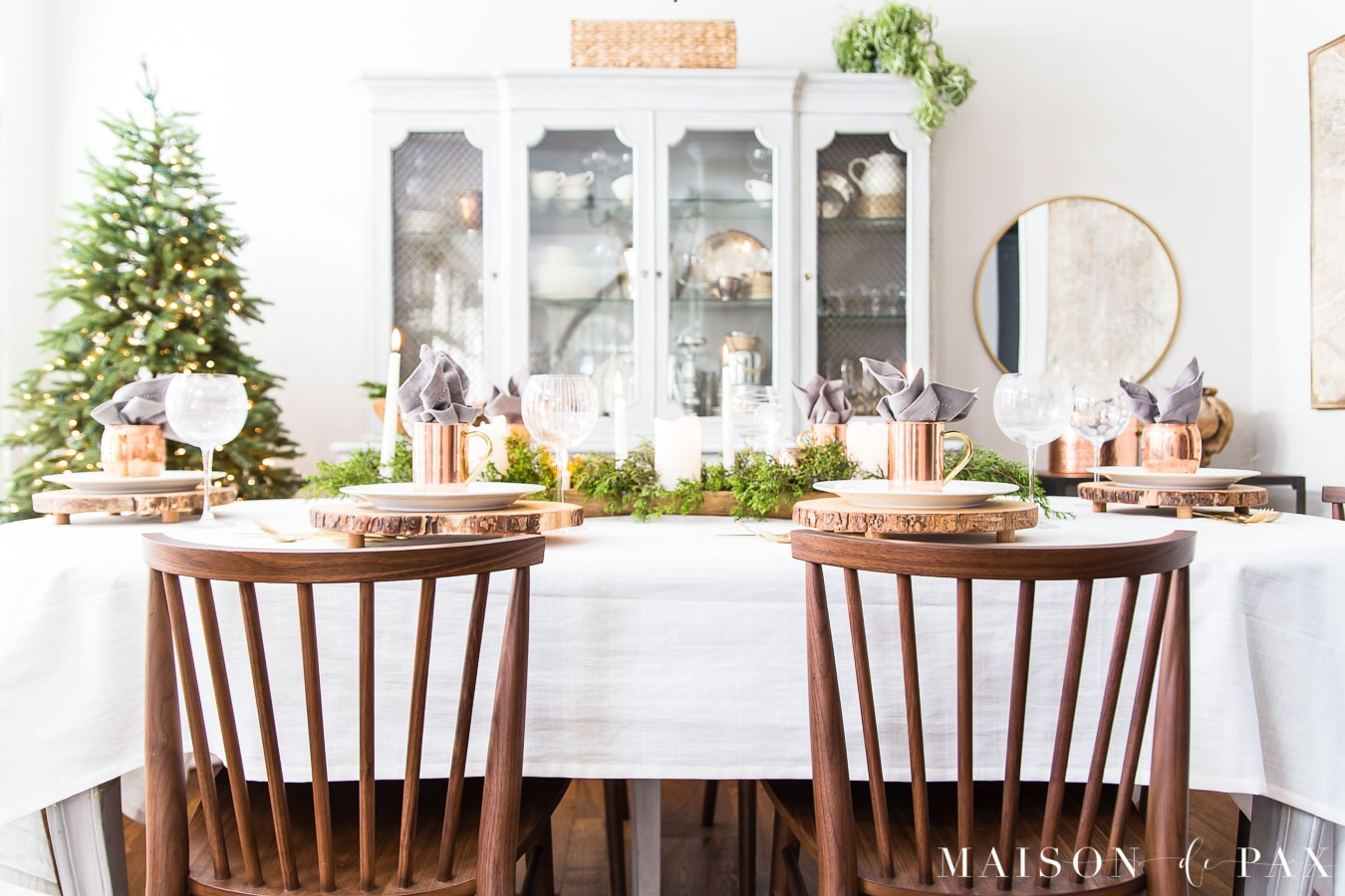 brown wood rung modern farmhouse chairs at a dining table with a white tablecoth