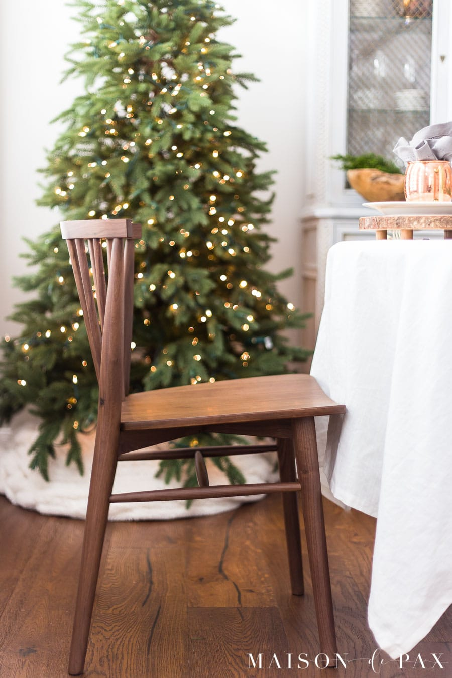 walnut modern farmhouse dining chair in front of green Christmas tree with lights