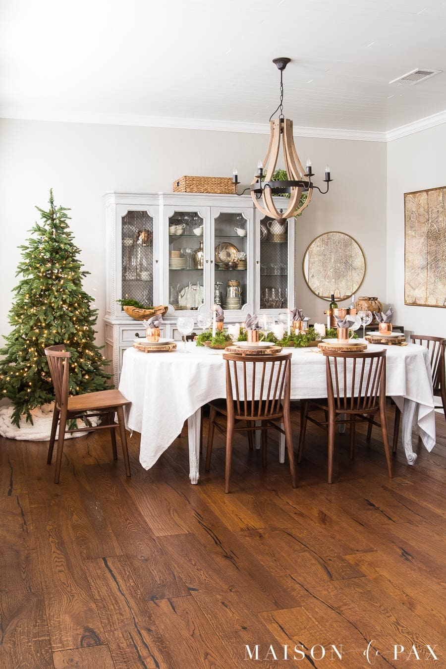 french country dining room with medium wood floors and a simple holiday tree