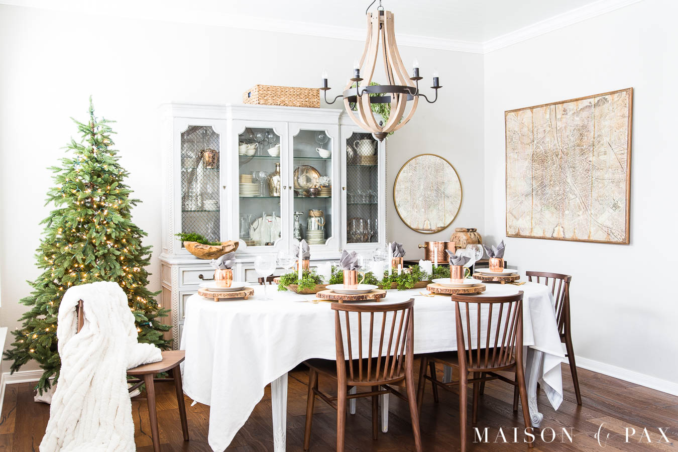 modern farmhouse dining room with walnut chairs and a simple green tree