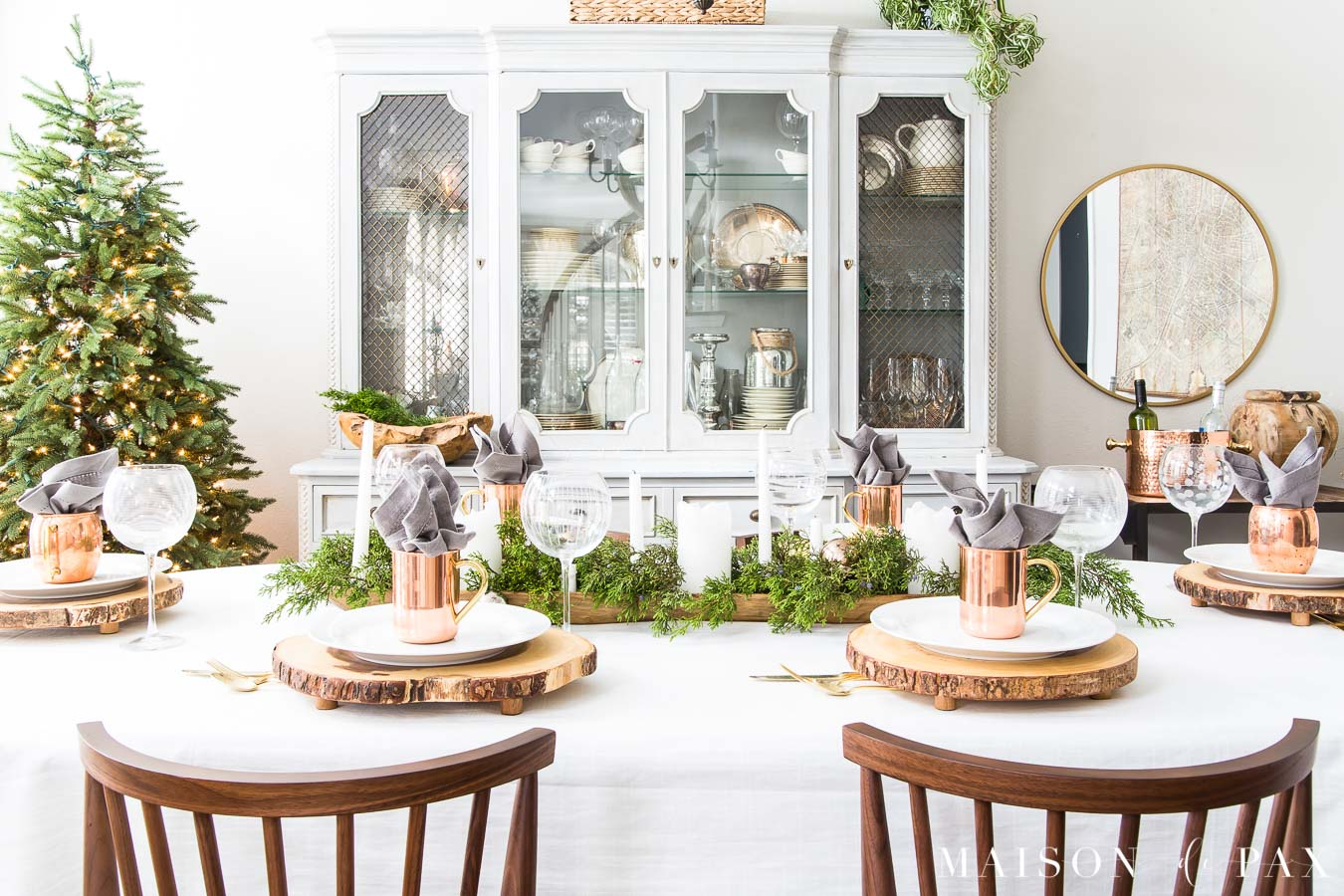 simple wooden chairs in the foreground with a dining table set with white tablecloth and holiday greenery lay beyond
