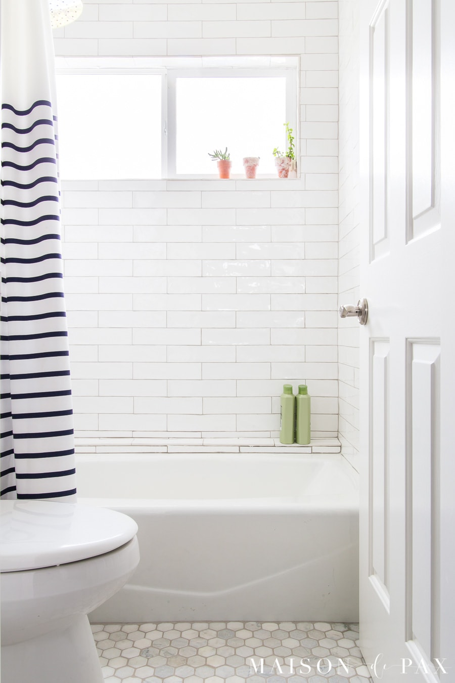 white tiled shower with navy and white striped shower curtain