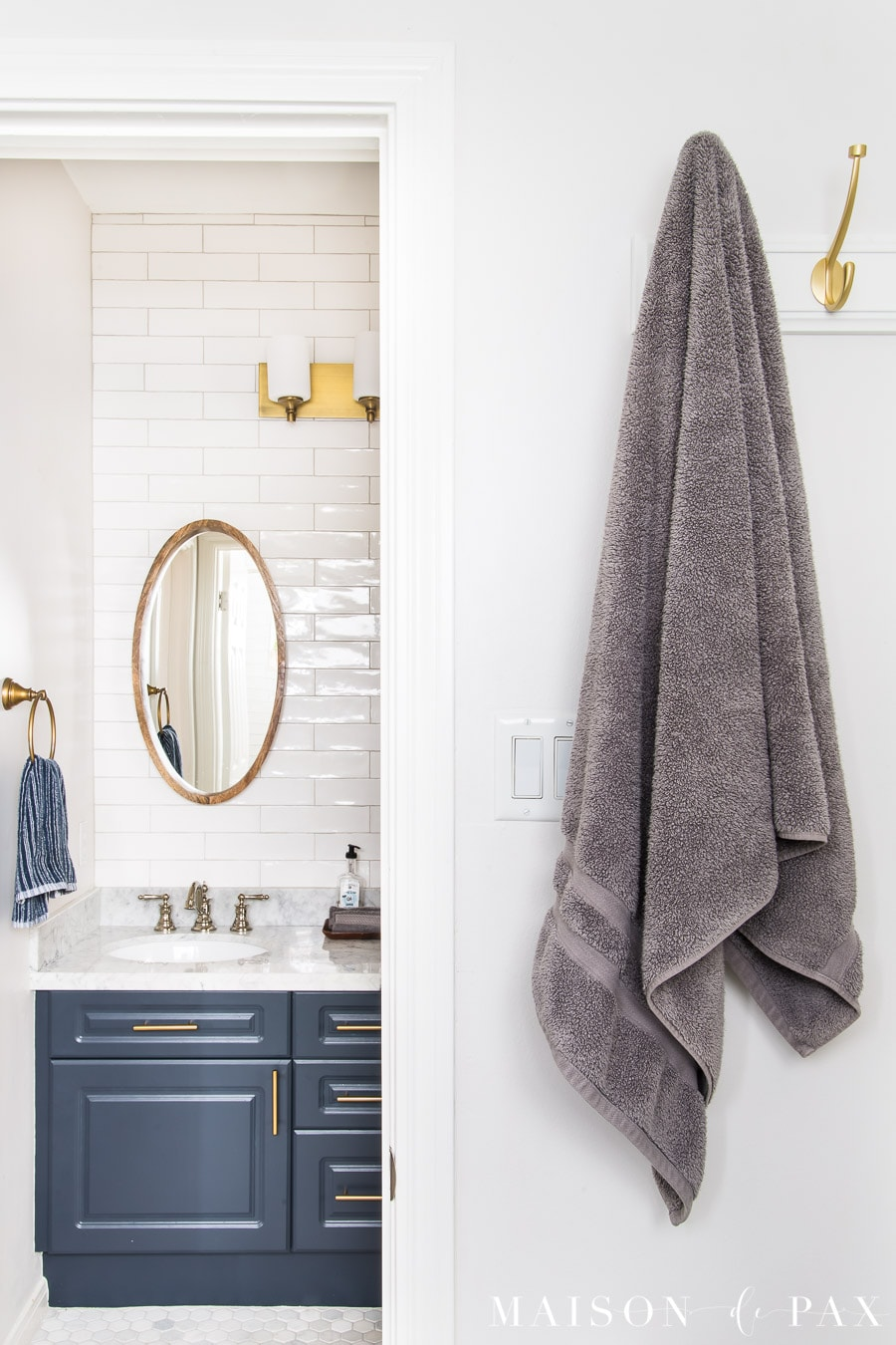 gray towel hanging from gold hooks with a navy vanity beyond
