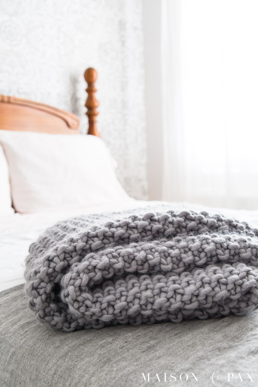 gray wool knit blanket on a white bed with an antique wood frame