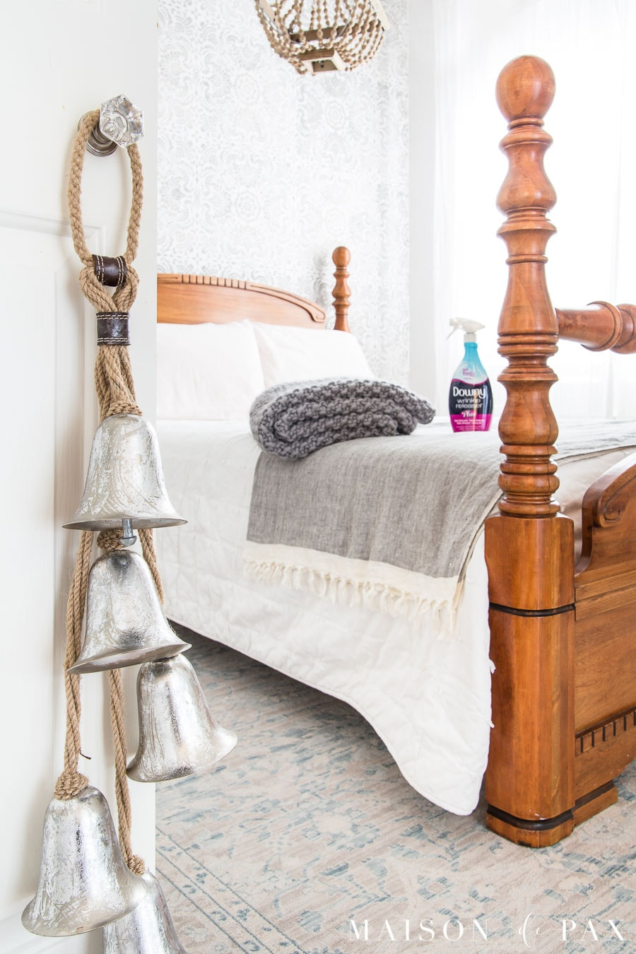 silver bells hanging on a closet door with an antique bed beyond