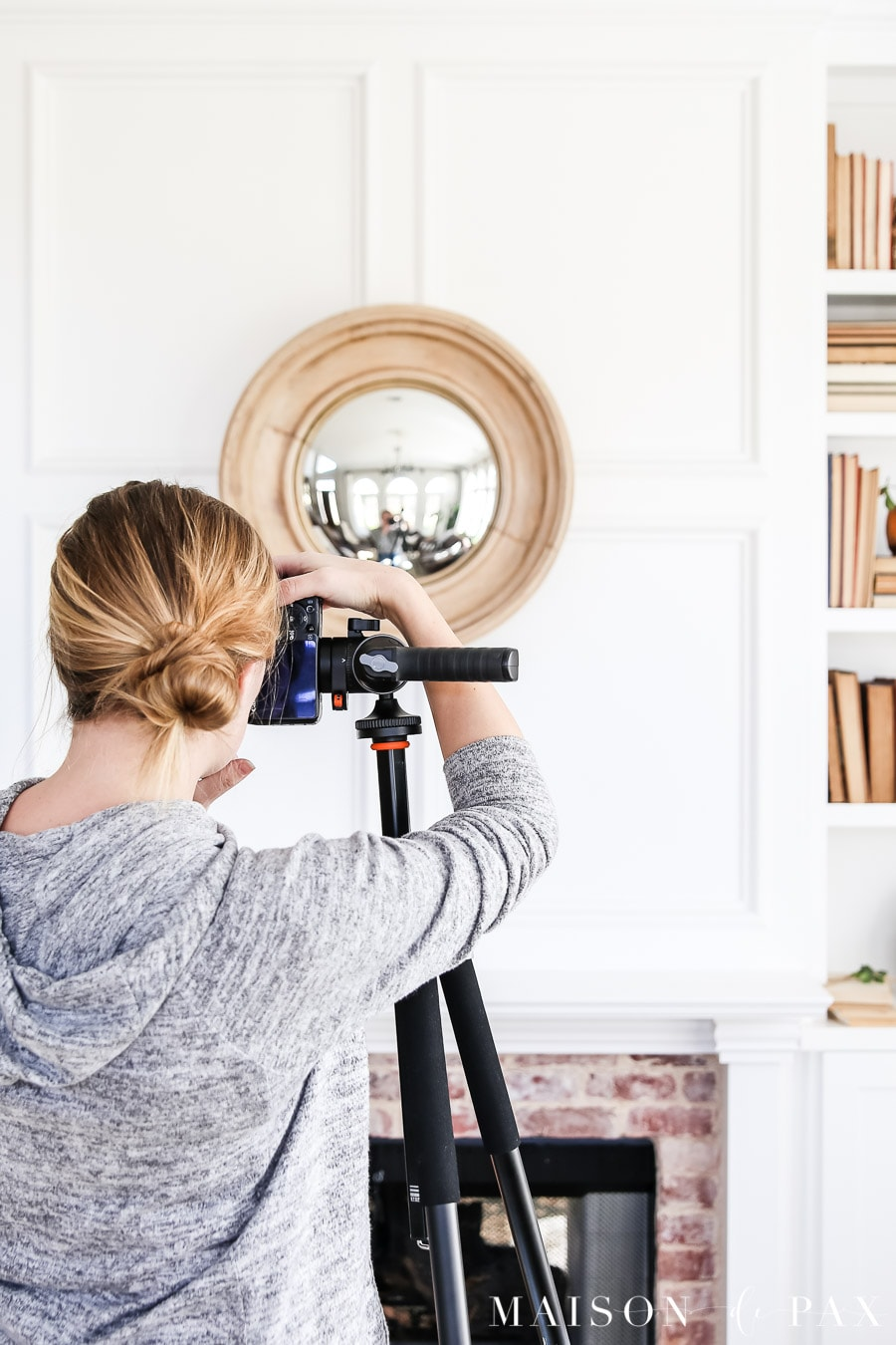 woman photographing fireplace using camera on tripod
