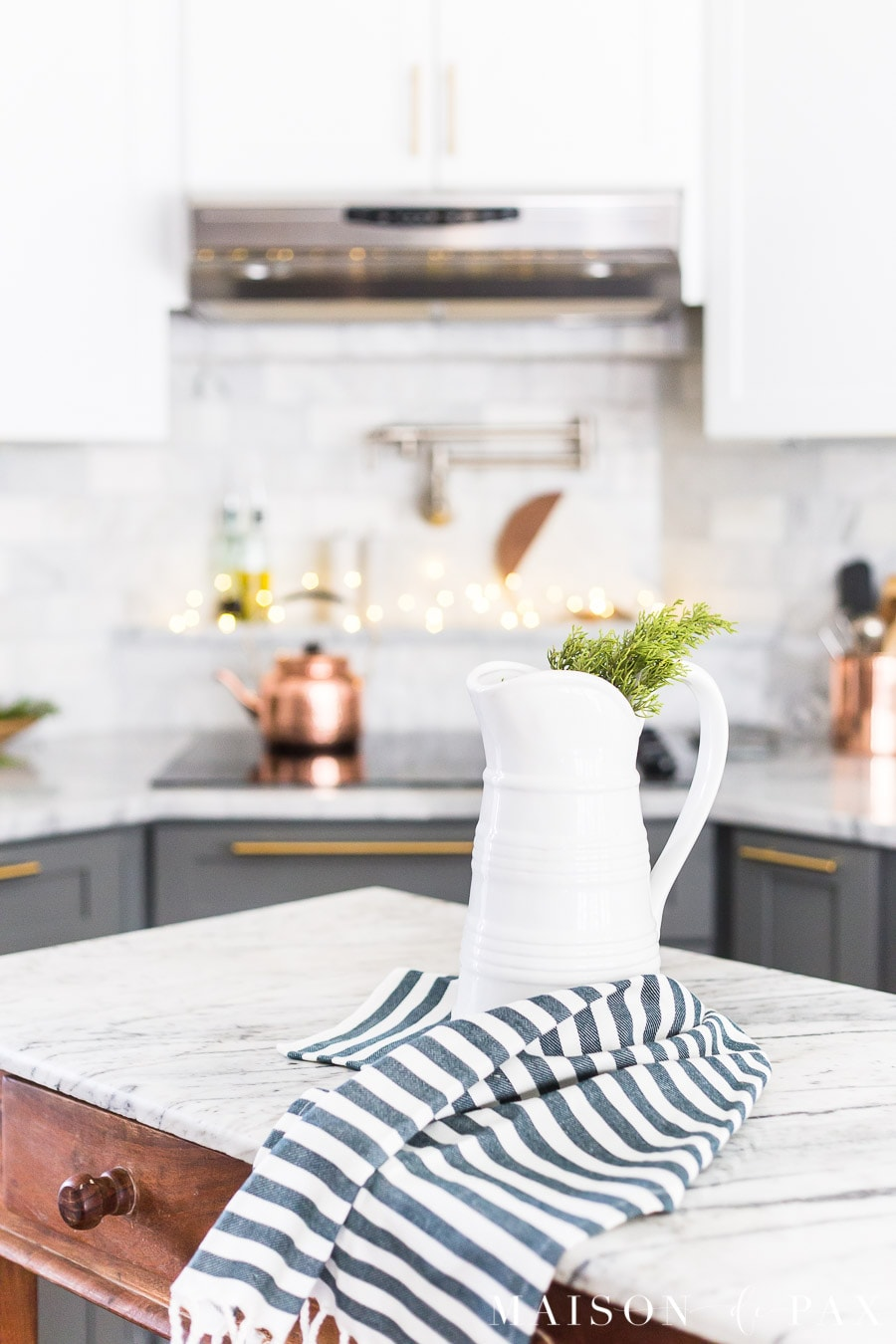 christmas kitchen: greenery in a farmhouse pitcher with a copper light strand in the background