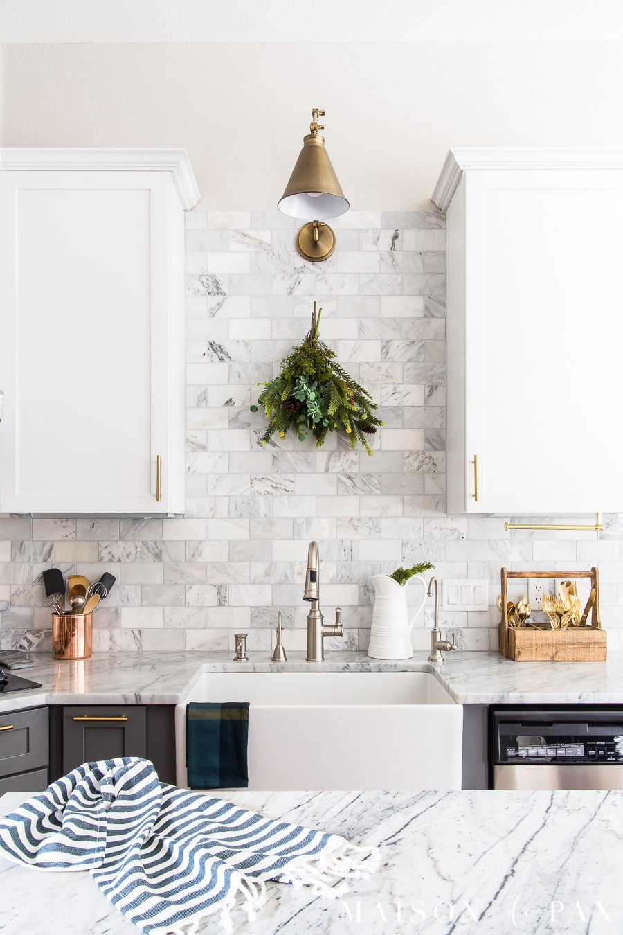 Marble Backsplash In A Two Toned Kitchen With Dark Green Holiday Accents