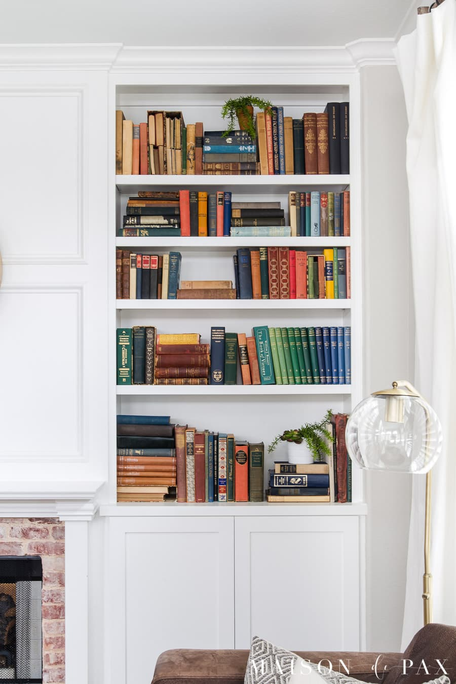 colorful antique books in white bookcase | Maison de Pax