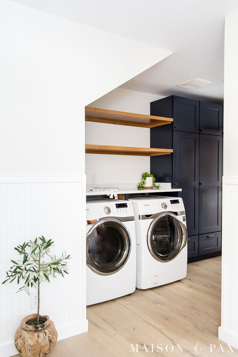 navy laundry room with wood shelves under stairs | Maison de Pax