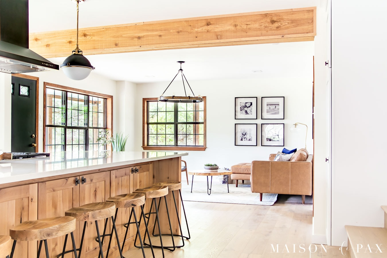 big island with wood barstools open to living room | Maison de Pax